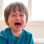 A young boy cries with his mouth open. In the background are some windows and furniture, slightly out of focus.