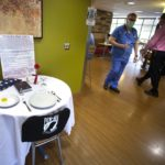 A fully set table is seen in the middle of a cafeteria. The chair is empty and has a POW-MIA banner. A folded American flag, Bible, single rose, candle and sign explaining the project are visible.