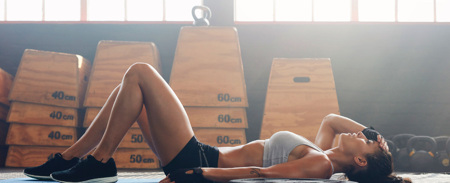 A female athlete rests on the floor, laying on her back, in this stock photo. Weights and other fitness equipment are visible behind her.
