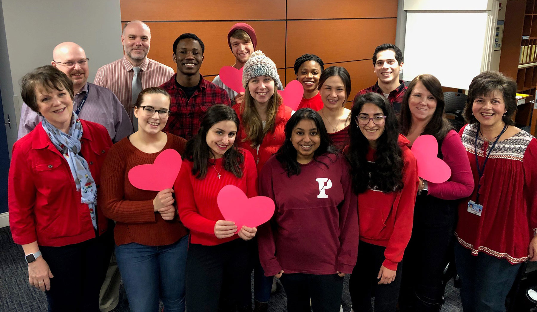 A photo shows a group of 15 people wearing various shades of red and holding cut-out paper hearts.