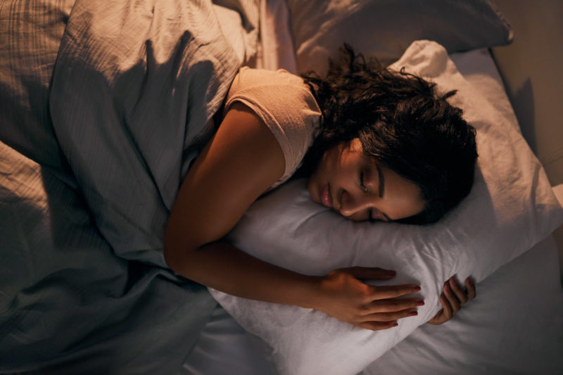 A woman lays in bed on her left side, under a comforter. Her eyes are closed and her arms are wrapped around a pillow.