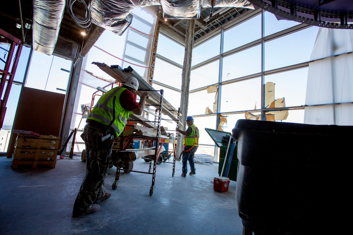 Construction workers work on the interior of a building