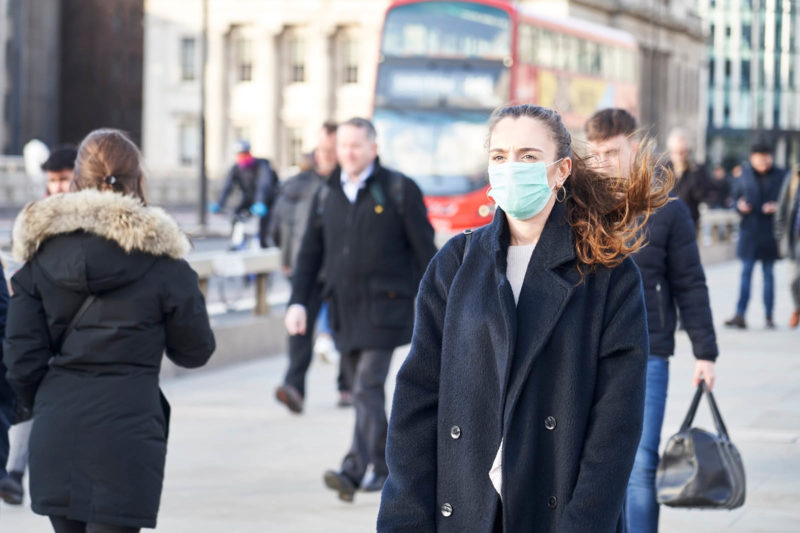 People walk down a city street, some wearing face masks, others not.