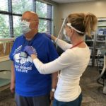 An exercise physiologist touches the back of an older male patient as he stands in St. Joseph's cardiac rehabilitation room. The man is wearing a heart monitor, a T-shirt and face mask. The exercise physiologist is wearing a long-sleeved shirt, a face mask and face shield.