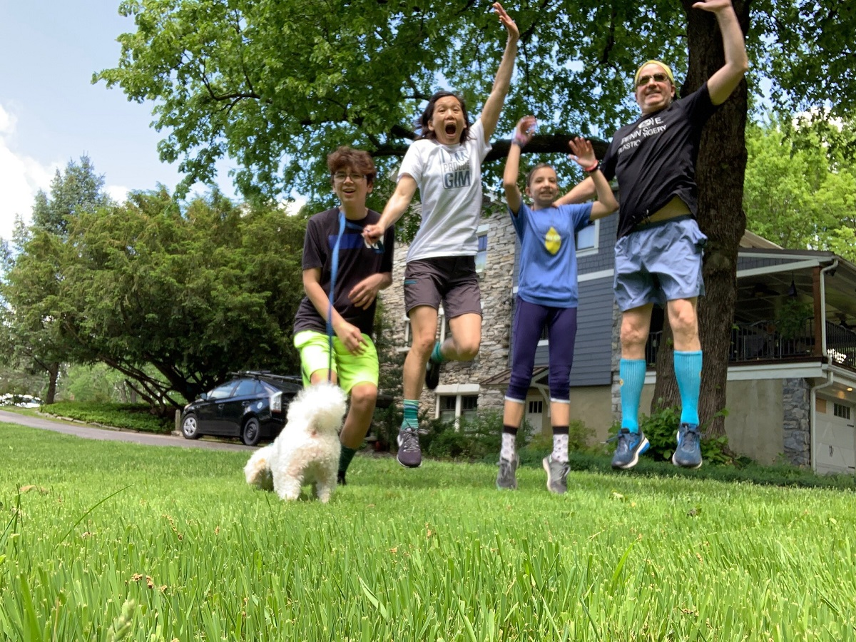 Four people jump off the grass outside of a house. One holds a dog on a leash.