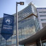 A blue and white flag hangs from a light pole in front of the entrance to Hershey Medical Center. On the flag is the Nittany Lion shield and the words, Penn State Health.]