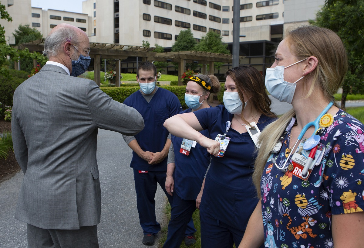 Gov. Tom Wolf, wearing a surgical mask and a suit, holds out an elbow to a woman in scrubs and a surgical mask, who offers her elbow in return. Three others in scrubs and surgical masks stand in a row. The widows and cement of Hershey Medical Center rise in the background.