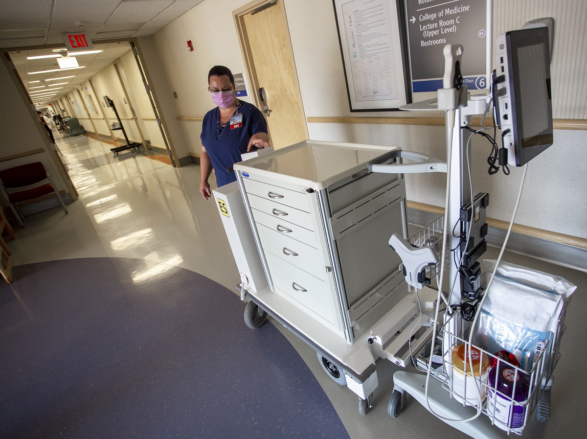 Tina Hedgepeth, a registered nurse at Hershey Medical Center, stands next to the motorized cart. One part is a huge cabinet on wheels with five drawers. It hitches to the other part, which includes baskets for storing items and a monitor mounted on a pole.