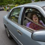 A woman in the passenger seat of a car smiles. Behind her, people line the roads and take photos.