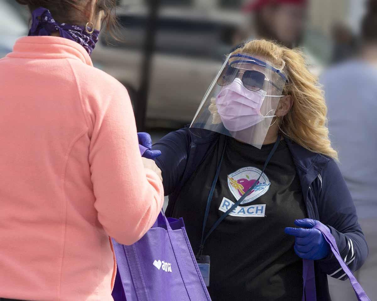 Madeline Bermúdez, con máscara, careta y gafas de sol, le entrega un bolso a una mujer con máscara.