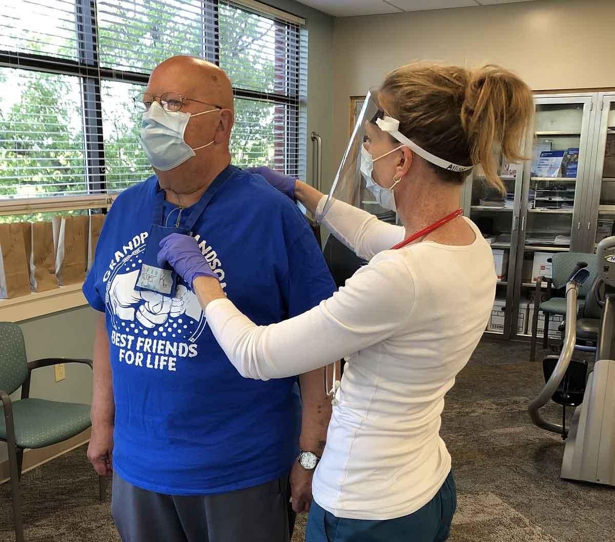 Un fisiólogo del ejercicio toca la espalda de un paciente masculino mayor que está parado en la sala de rehabilitación cardíaca de St. Joseph. El hombre lleva un monitor cardíaco, una camiseta y una máscara facial. El fisiólogo del ejercicio lleva una camisa de manga larga, una mascarilla y una careta.