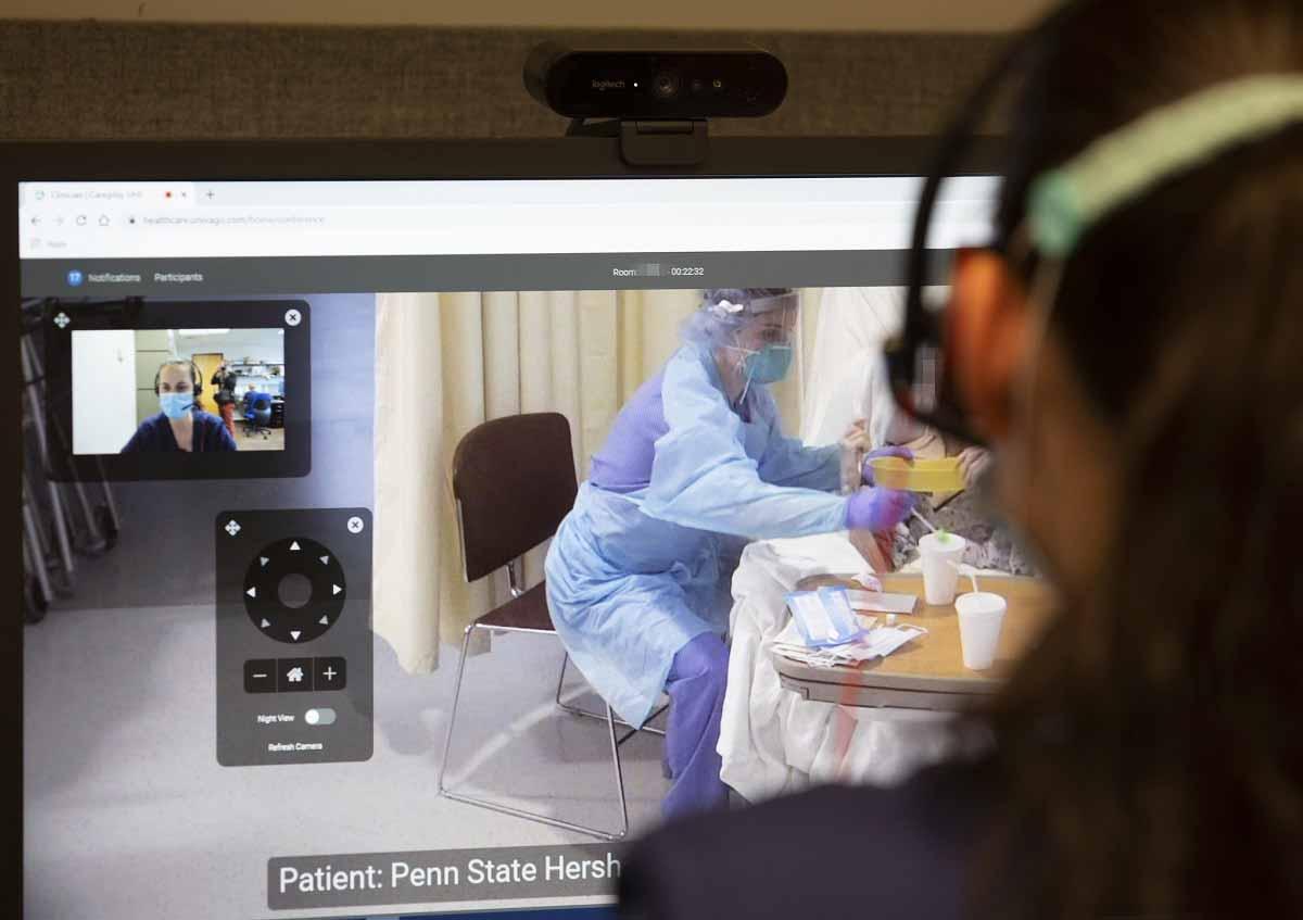 La imagen muestra sobre el hombro a alguien mirando el monitor de una computadora. En una ventana del monitor está la vista de alguien con una máscara. A la derecha, alguien con equipo de protección personal trabaja con un paciente.