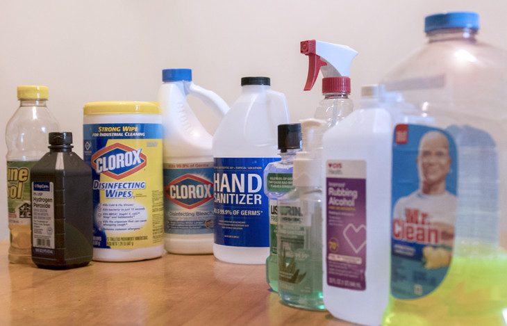 Ten household cleaners are pictured sitting on a table. They include Pine-Sol, hydrogen peroxide, Clorox disinfecting wipes, Clorox bleach, hand sanitizer, Listerine, rubbing alcohol, Mr. Clean and others.