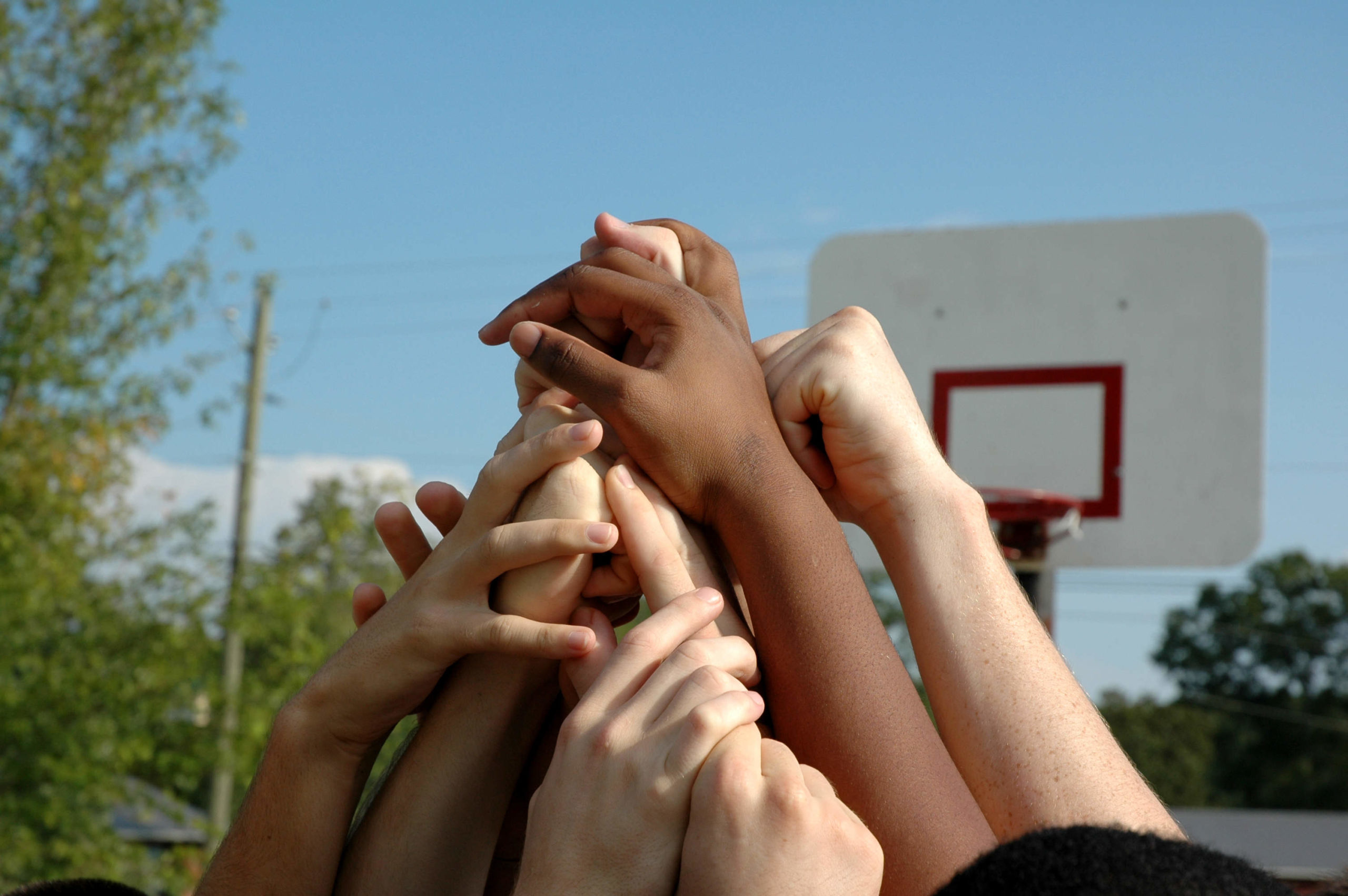 Close-up of several children extending their arms into the air to form a pyramid. In the background are trees, power lines and a basketball hoop.