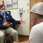 A male physician wearing a tie, Penn State Health coat, face mask and stethoscope, gestures with his hands while talking with a man seated across from him in a clinic room.