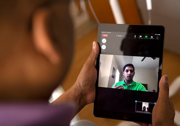 An image is taken from over the shoulder of ap erson. The person is holding an iPad, and the image of a student is on the screen.