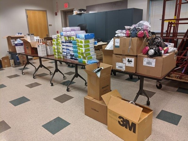 Boxes are seen sitting on a table, which is full. More boxes are on the floor. They are all filled with personal protective equipment.