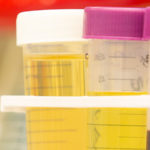A close-up image of laboratory equipment depicts test tubes, boxes and bottles on the shelf in a Penn State College of Medicine laboratory in summer 2016. Test tubes and one bottle are visible at left in focus, with other bottles out-of-focus to the right.