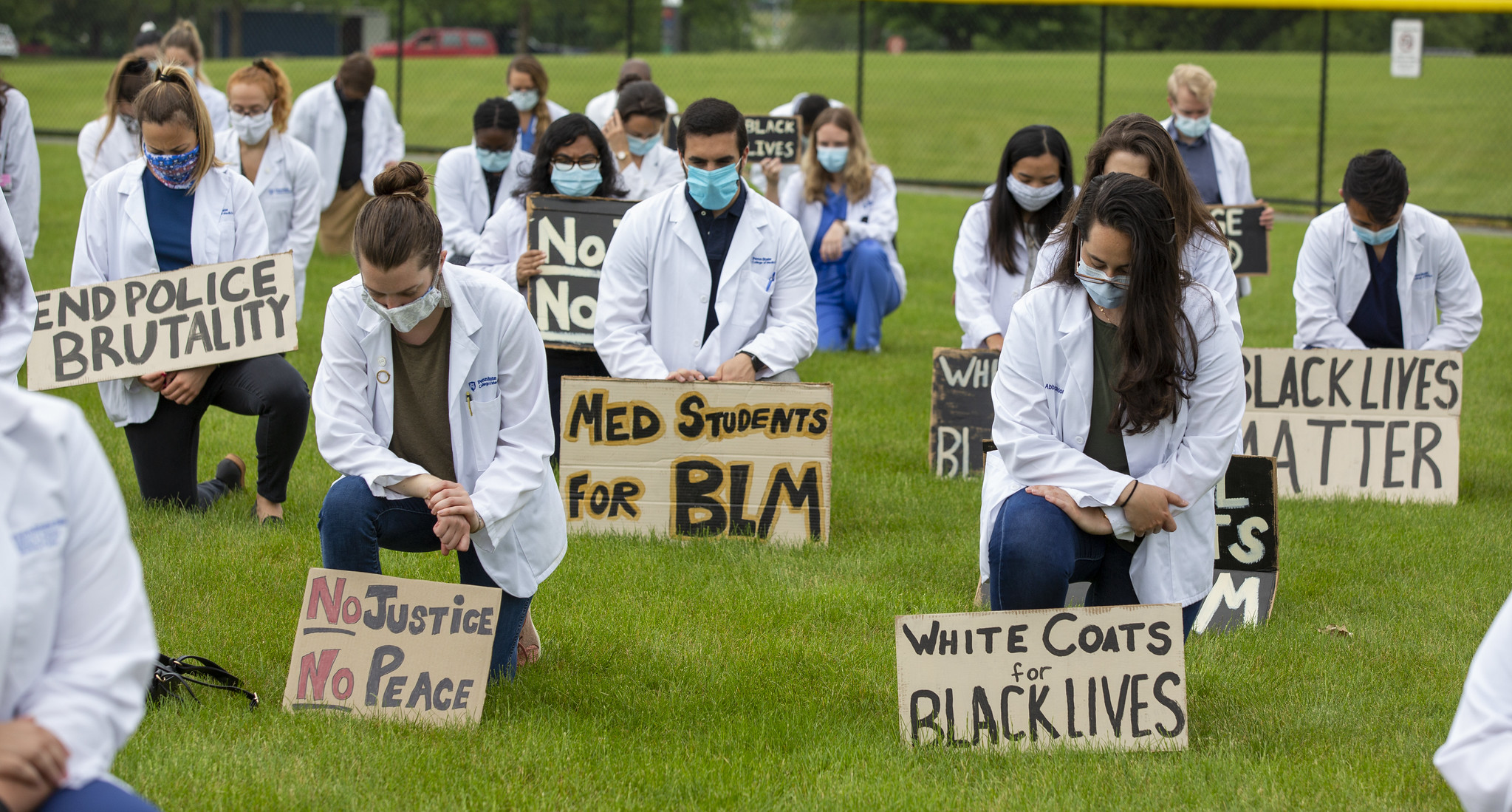 A group of people are seen spaced apart, kneeling on a green lawn. They hold signs with statements such as White Coats for Black Lives, No Justice No Peace, End Police Brutality, Black Lives Matter and Med Students for BLM.