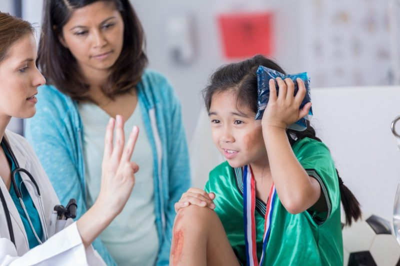 Serious female ER doctor holds up three fingers while talking with injured female elementary age soccer player. The doctor is asking the girl how many fingers she is holding up. The girl is wearing a medal and soccer uniform.