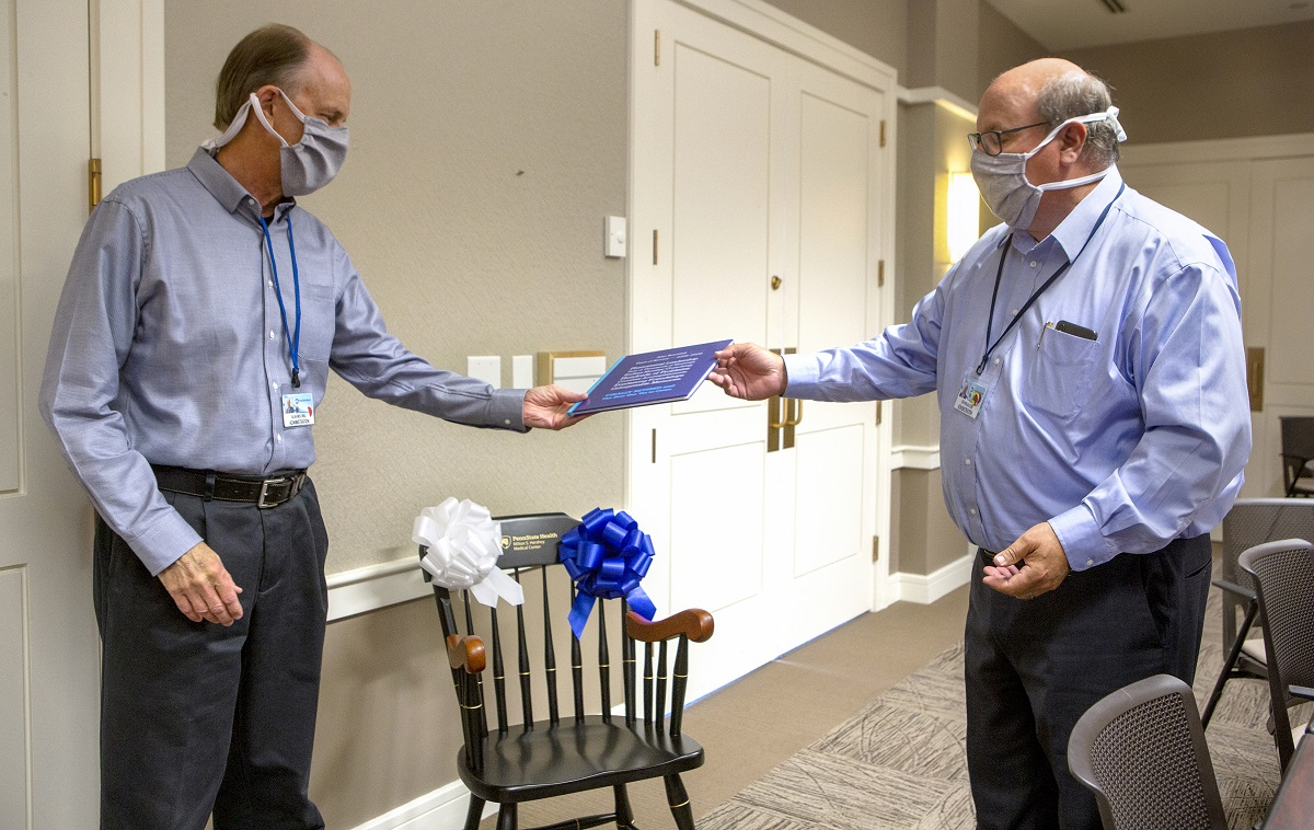 Penn State Health CEO Steve Massini hands a memory book to Alan Brechbill. Both men are wearing dress shirts, trousers and masks. A chair with a Penn State Health Milton S. Hershey Medical Center logo and two bows on it is in the background.