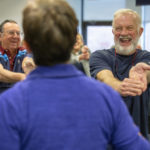 Hank Shipman smiles broadly as he stretches his arms out in front of himself and bends down his fingers. He wears a T-shirt and has a beard and moustache. Other rehab patients smile and laugh in the background as they do similar stretches. The instructor is seen from behind.