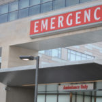 "A close-up image of a large sign reading ""EMERGENCY"" at the Hershey Medical Center Emergency Department entrance."