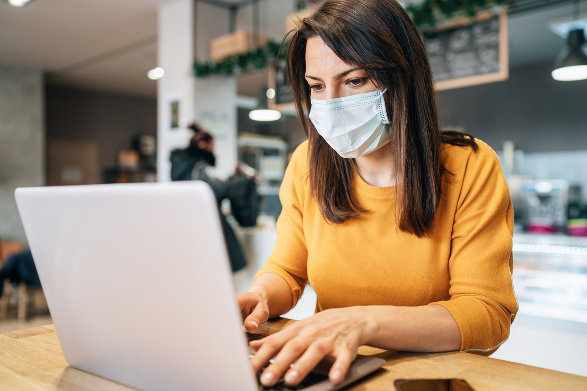 A woman in a face mask is sitting at a desk using a laptop.