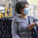 A woman sits on a bus, with her left arm resting on the window rail. She looks out the window. She's wearing a surgical mask.