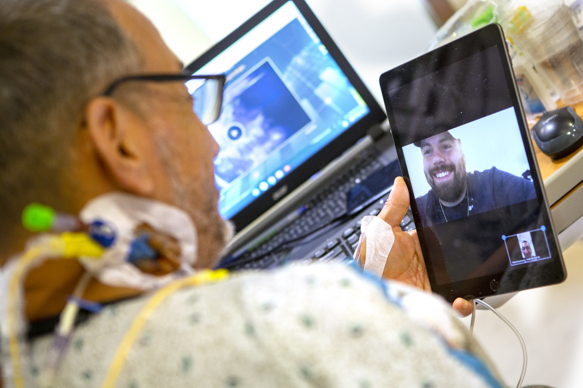 A man in a hospital gown in his hospital bed holds up an iPad on which a man is smiling back at him. A laptop computer is in the background, slightly out of focus.