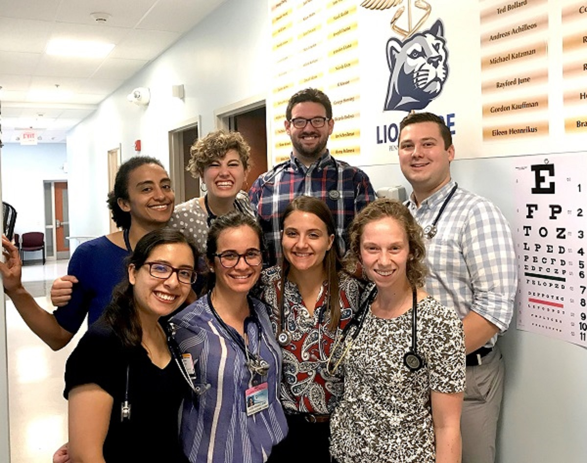 Eight physician assistant students from the Class of 2022 strike a pose at LionCare, Penn State College of Medicine's free student-run clinic at Bethesda Mission, a shelter for homeless people in Harrisburg. Each student is smiling and has a stethoscope wrapped around their neck.
