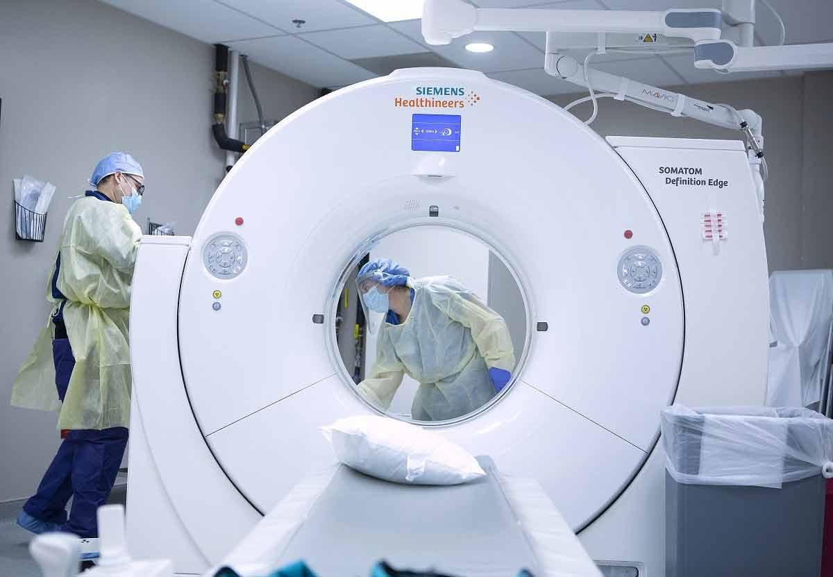 Un hombre y una mujer con máscaras faciales, guantes y fundas desechables para el cuerpo y la cabeza desinfectan una sala de tomografía computarizada después de ser utilizada por un paciente COVID-19 en el Centro Médico St. Joseph.