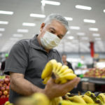 A man stands in the produce section of a grocery store, holding up a bunch of bananas and looking at them. He is wearing a face mask. Other shoppers are in the background.