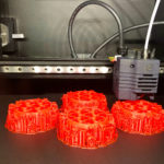 Four large models of COVID-19 viruses that have been made with a 3D printer are seen with the printer in the background.