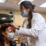 A woman in a white physician's coat looks at the top of a patient's head