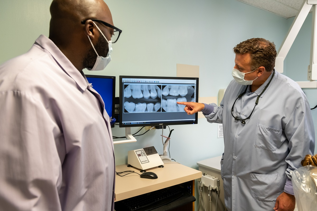 Dr. Larry Trubilla, wearing a lab coat and glasses hanging from his neck, points at the illuminated X-Ray image of a set of teeth. Dental resident Jowhar Brown, wearing glasses and a surgical mask, looks on.
