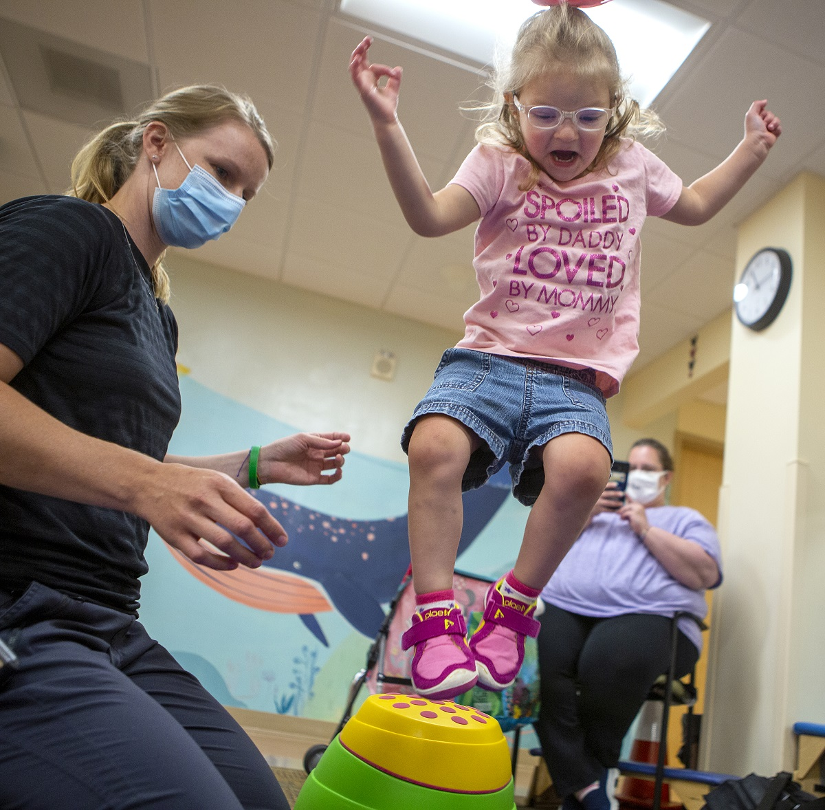"Joella Migliori jumps over a plastic stepping stone in a physical therapy room. Physical therapist Emily Hoffman, who has her hair in a pony tail and wears a face mask, kneels beside her. Joella, who wears glasses and has short hair pulled back in a barrette, wears a T-shirt that says ""Spoiled by Daddy, loved by Mommy"" with shorts and sneakers. Janette Migliori, Joella's mother, sits in a chair in the background and holds up to phone to take a picture."
