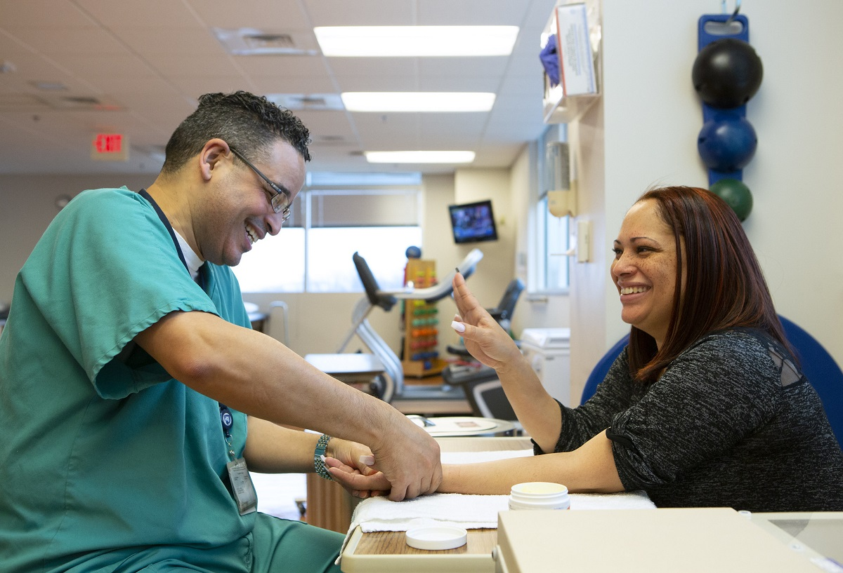 St. Joseph occupational therapist Julio Torres, left, smiles as he touches the hand of patient Diana Espinosa. Torres is wearing scrubs and glasses. Espinosa has long hair and is wearing a top with lacy sleeves. Behind them are balls hanging on the wall and a therapy bike.