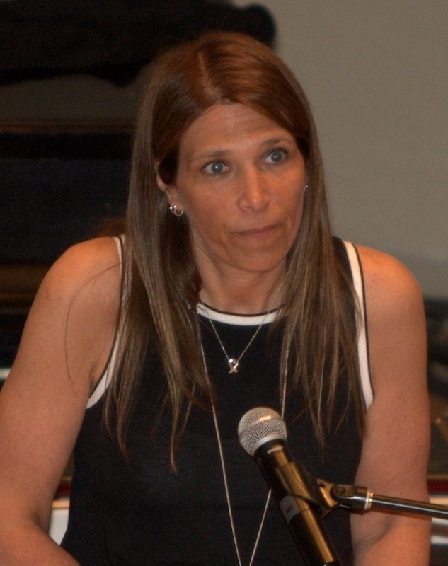 A woman with long hair stands at a podium.