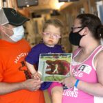 Jon Beckner, wearing a baseball cap and a T shirt, hold a little girl in pigtails and glasses. His wife holds the little girl from the other side. They also hold two sides of a photo of a premature baby with in a knitted cap.
