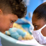 Side profile as a young child and an adult look each other in the eyes, each bearing a serious expression. A hospital bed is in the background, out of focus. At the bottom are logos for Penn State Children's Hospital and CMN.