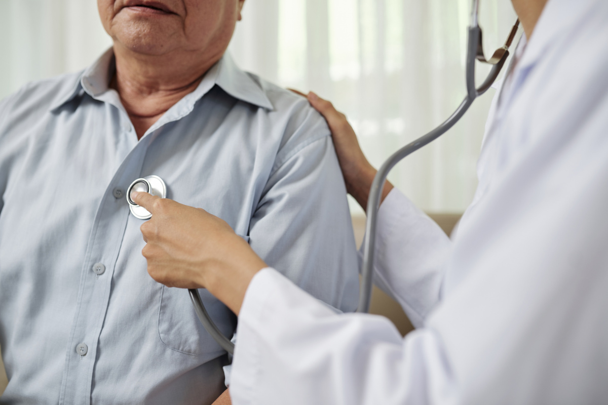 A medical professional wearing a stethoscope holds a stethoscope to the left side of a male patient's chest. Her right hand rests on the patient's shoulder.