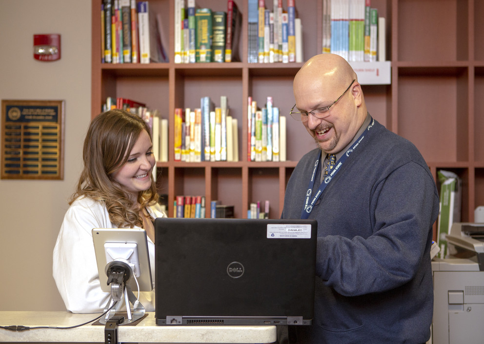 A man and a student are seen looking at a computer in a library.