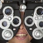 A close-up of a young child looking through the lenses of eye examination equipment, which contains several dials.