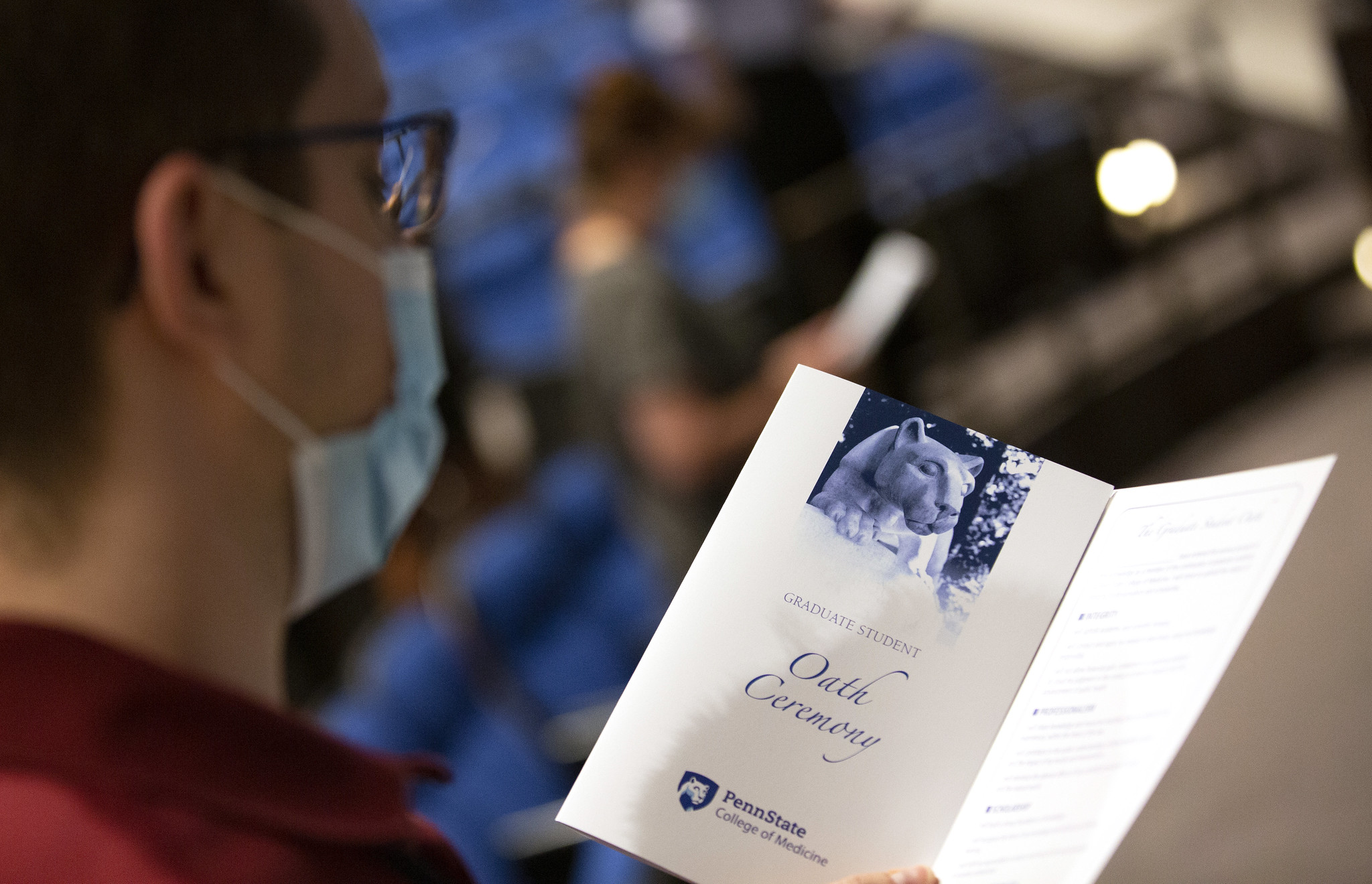 "A man in glasses looks at a piece of paper. On the paper are the words ""Oath ceremony"" and a rendering of the Penn State Nittany Lion."