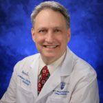 Dr. Lawrence Sinoway, cardiologist and director, Penn State Heart and Vascular Institute, wearing cream-colored dress shirt, red tie and white Penn State Health Milton S. Hershey Medical Center lab coat.