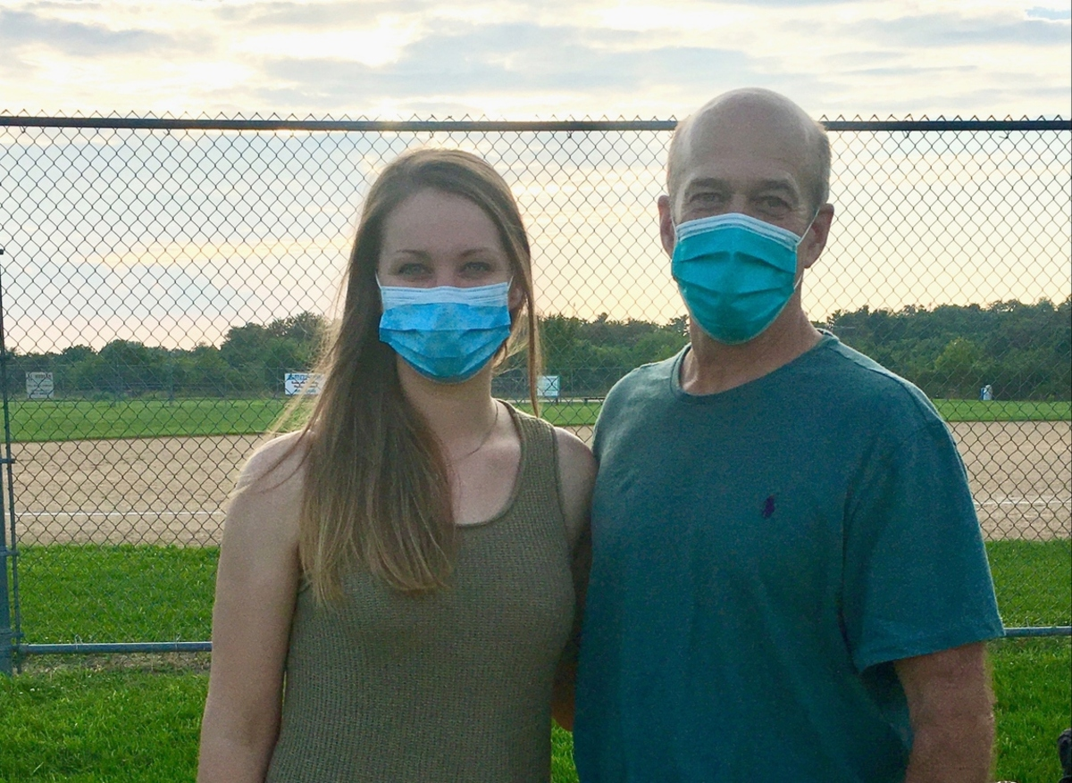Shalisa Walker stands arm in arm with John Dohner in front of a chain link fence at a softball field. Walker has long hair and wears a tank top. Dohner, who is bald, wears a T-shirt. Both are wearing masks.