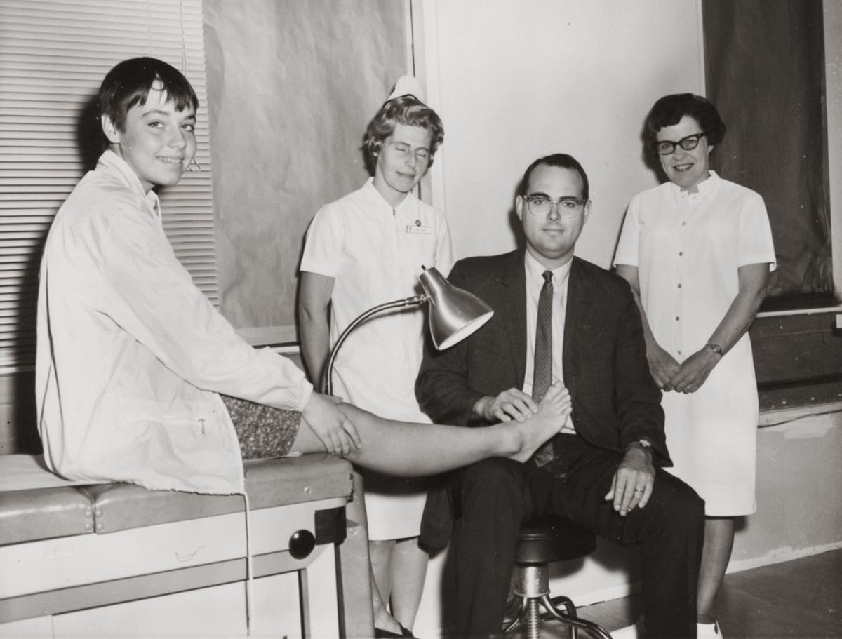 Dr. Willis W. Willard III, wearing a suit and tie, holds the foot of a young boy on an exam table. Two nurses, dressed in white dresses and nursing caps, stand in the background. The boy wears shorts and a jacket and is smiling.