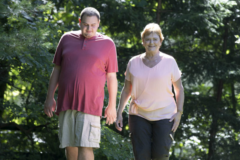 Man in red shirt and tan cargo shorts walks alongside woman in pink top and black pants in a wooded yard
