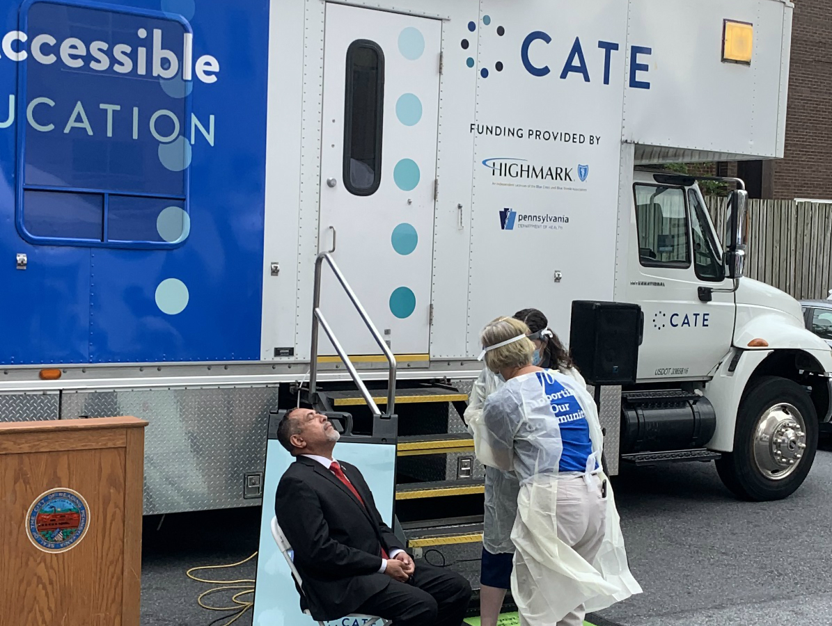 Eddie Moran leans back in a chair while two women in PPE stand in front of him. Behind them is a truck with the word CATE on the side.